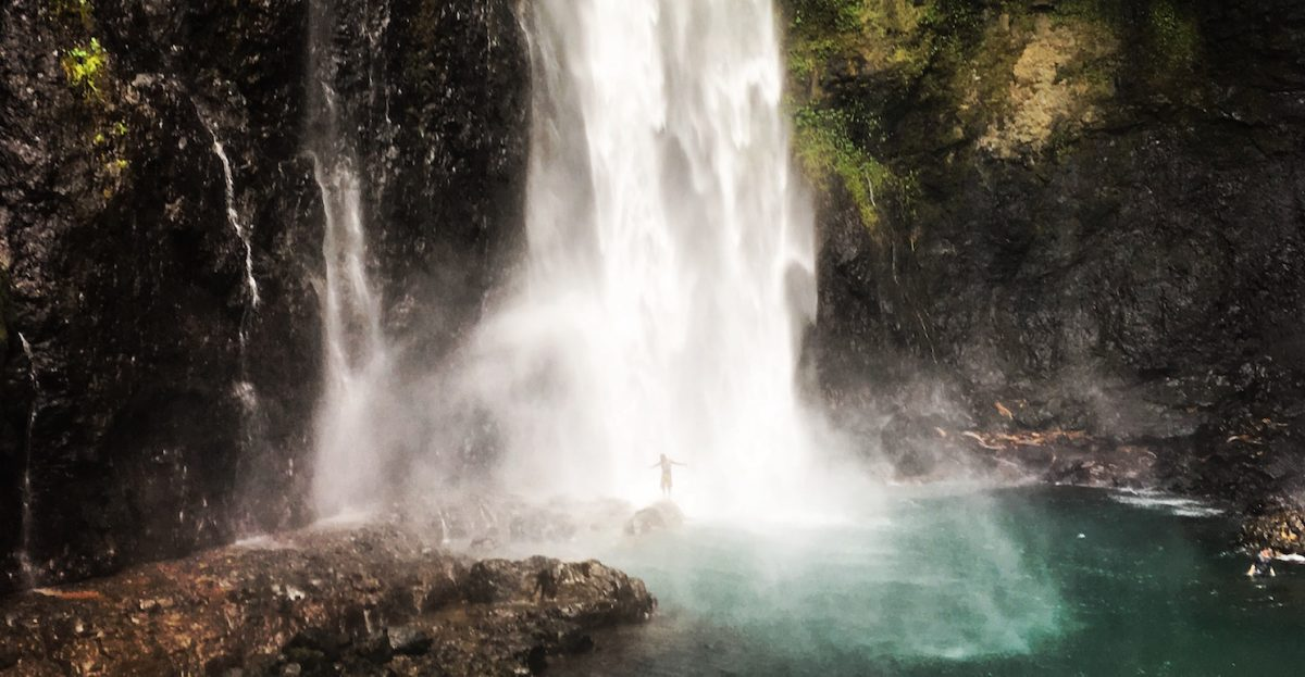 Figure under waterfall