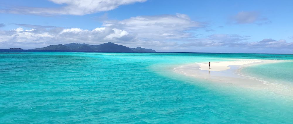 Photo of sandbank in turquoise sea,Beqa Island on horizon. The invisible space between people and their immediate environment.